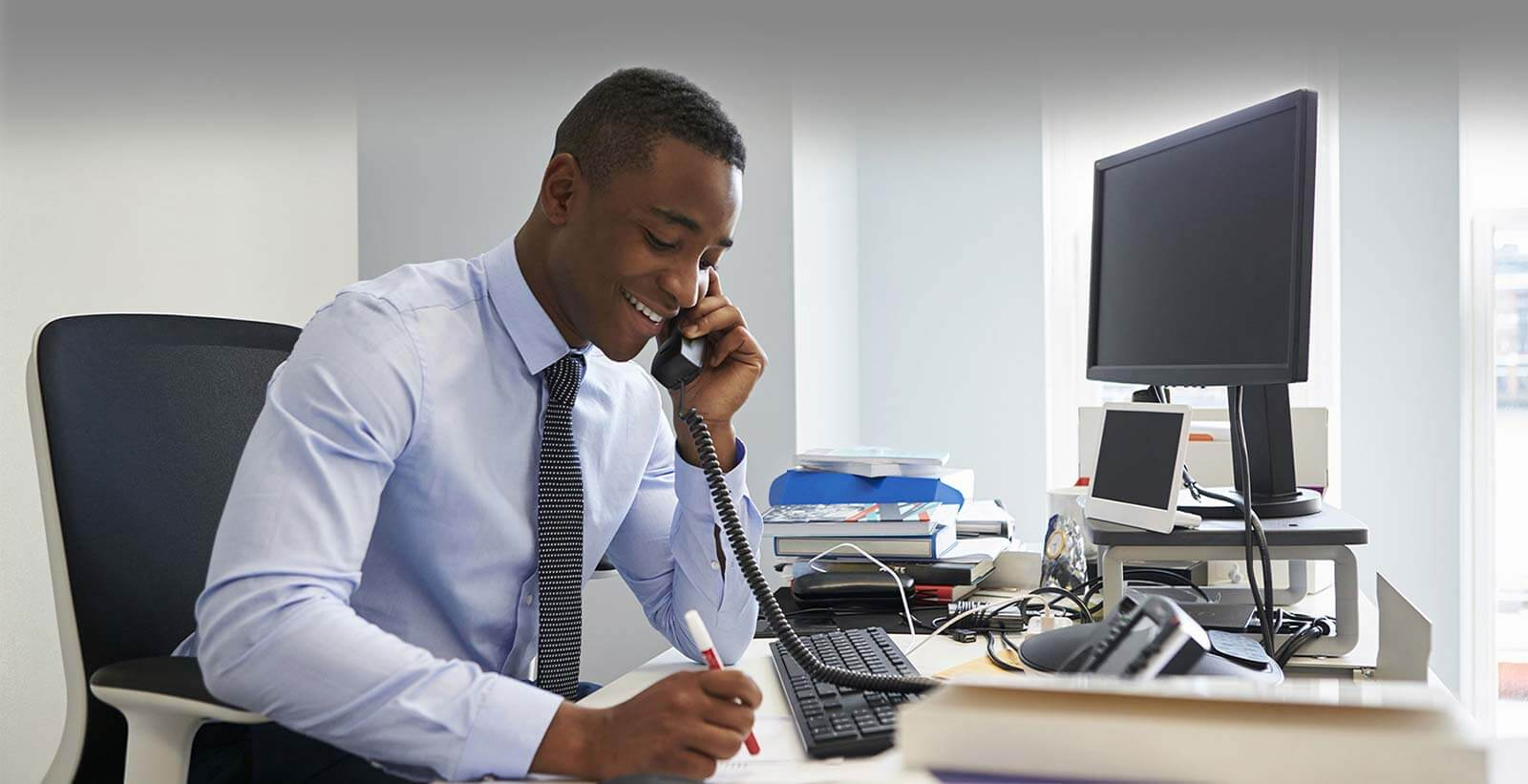 Vision voice & data young black businessman using the phone at his office desk